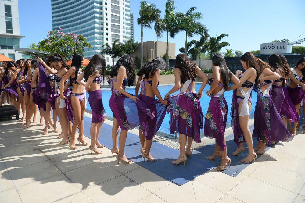 Garotas se juntam ao redor da piscina vestindo biquínis e cangas