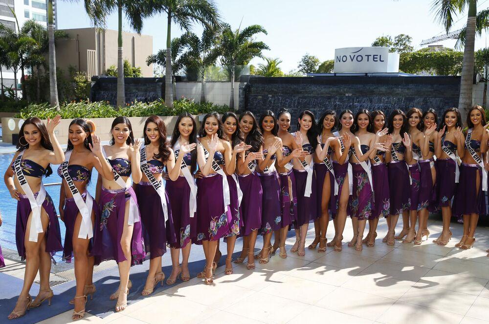 Morenas que pretendem participar no concurso de beleza Miss Filipinas cumprimentam o público, posando perto da piscina