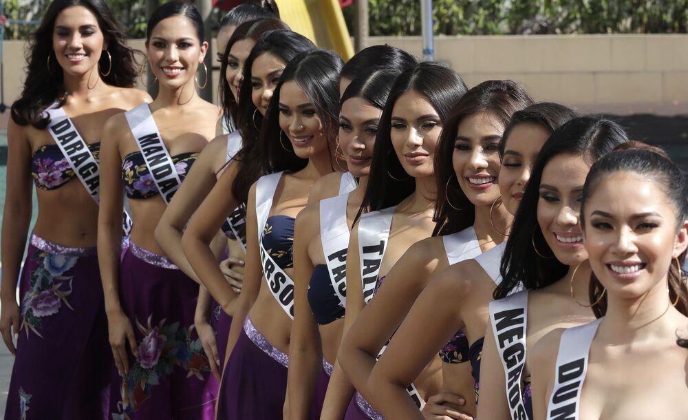 As candidatas do concurso de beleza sorriem para as câmeras de jornalistas