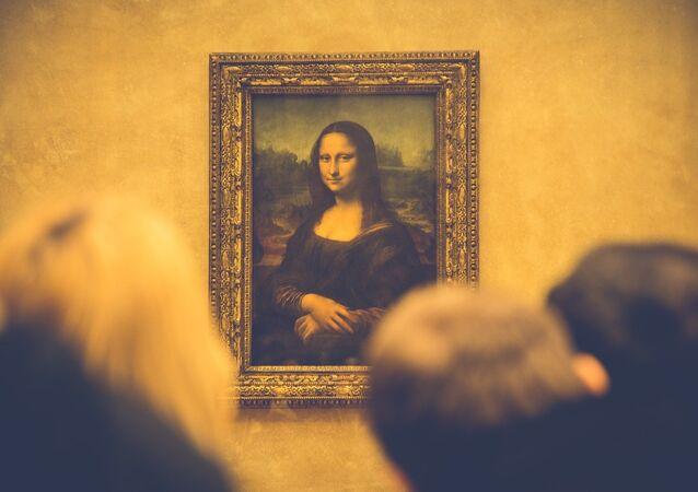 Pessoas observam a obra de Leonardo Da Vinci, Mona Lisa