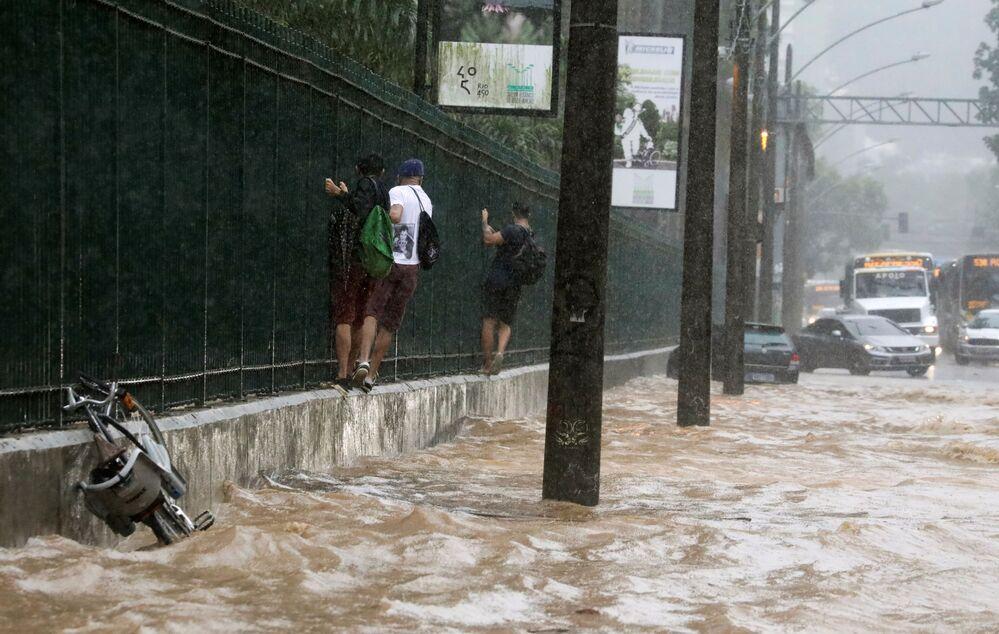 Moradores se seguram em grade para atravessar rua alagada no Rio de Janeiro