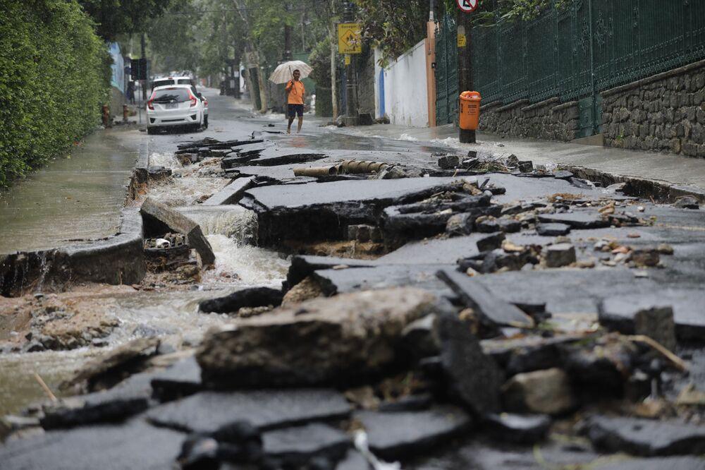 Homem caminha em rua danificada por fortes chuvas