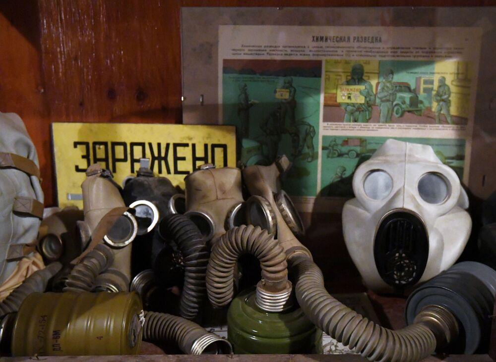 Máscaras de proteção contra radiação e cartaz de instrução do que fazer em caso de ataque radioativo são expostos no museu subterrâneo Bunker 703
