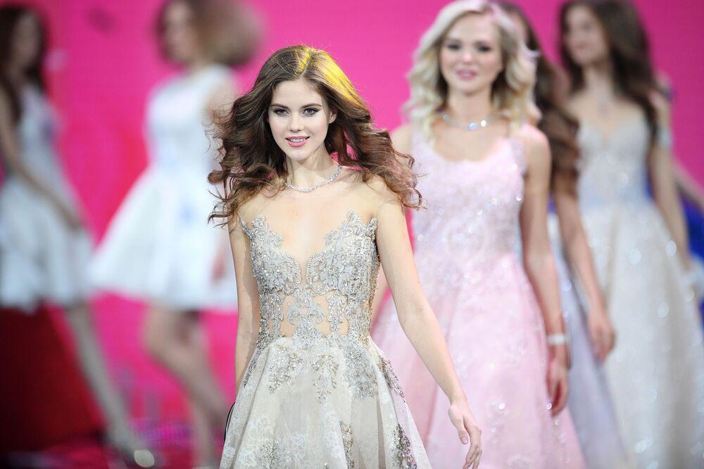 Concorrente do concurso Miss Rússia 2019 desfila na passarela em vestido de gala, Rússia, 13 de abril de 2019