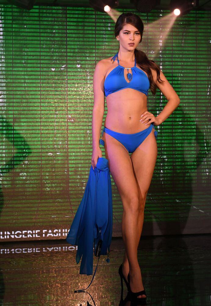 Modelo desfila com biquíni azul durante apresentação do desfile de peças íntimas Lingerie Fashion Week, Moscou, Rússia