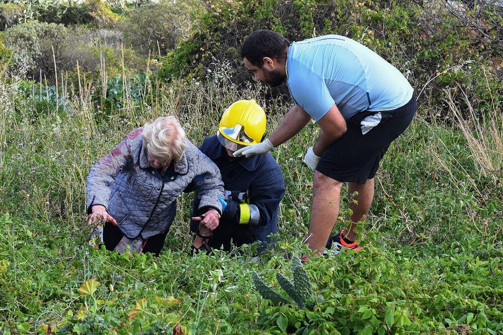 Bombeiros ajudam uma vítima após acidente com um ônibus na Madeira