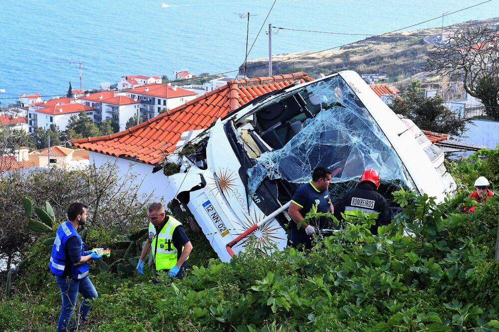 Bombeiros e equipes de resgate ao lado de ônibus caído em um barranco na ilha da Madeira