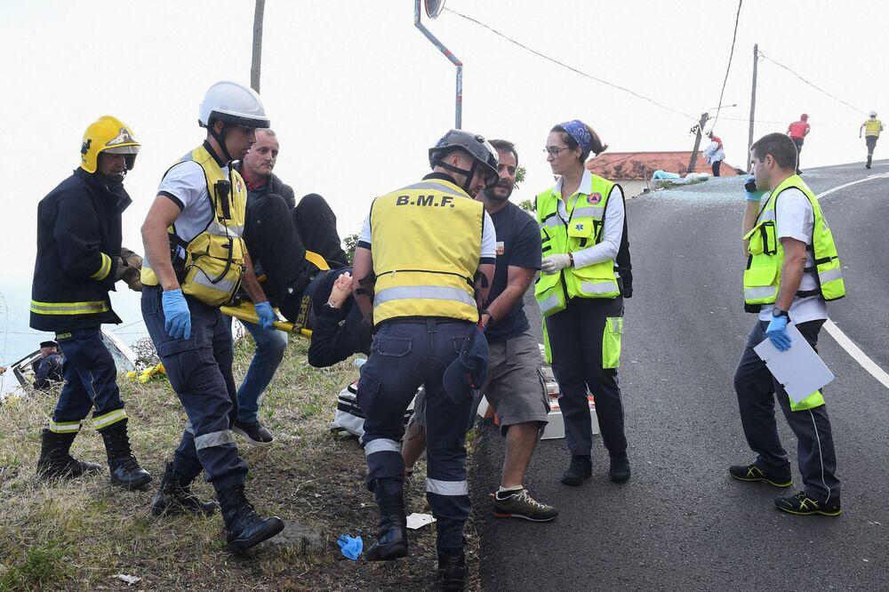 Bombeiros e equipes de resgate ajudando vítimas do acidente com ônibus turístico na Madeira