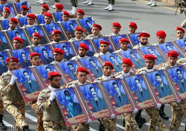 Representantes do Corpo de Guardiões da Revolução Islâmica (CGRI) desfilam com retratos de heróis mortos em guerras passadas (arquivo)