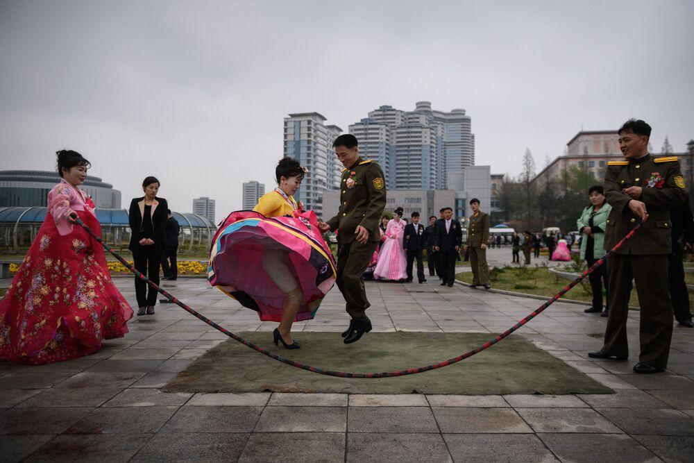 Noivos pulam corda durante sessão de fotos de casamento em um parque de Pyongyang, Coreia do Norte, 18 de abril de 2019