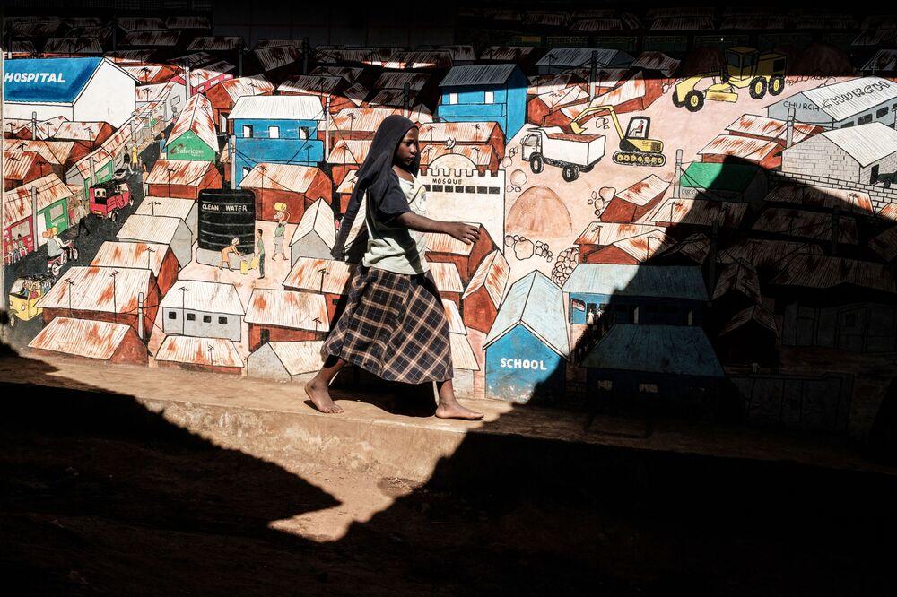 Mulher passa por parede com grafites nas favelas de Kibera, em Nairobi, 16 de abril de 2019