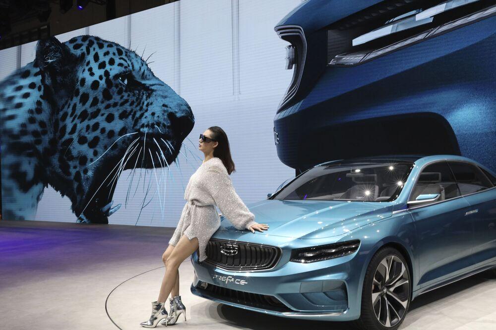 Mulher posa ao lado de um sedan Preface, da empresa chinesa Geely Auto, durante exposição em Xangai, China, 16 de abril de 2019