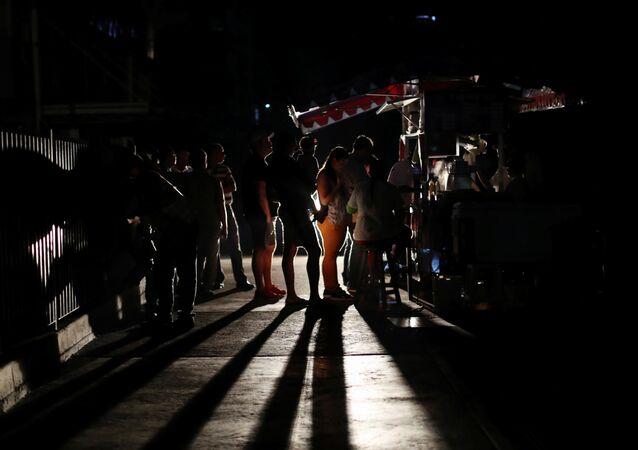Moradores se reúnem durante um apagão em Caracas, Venezuela.
