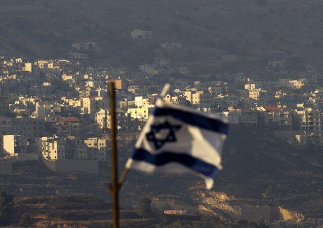 Bandeira israelense em frente à aldeia de Majdal Shams nas colinas de Golã controladas por Israel