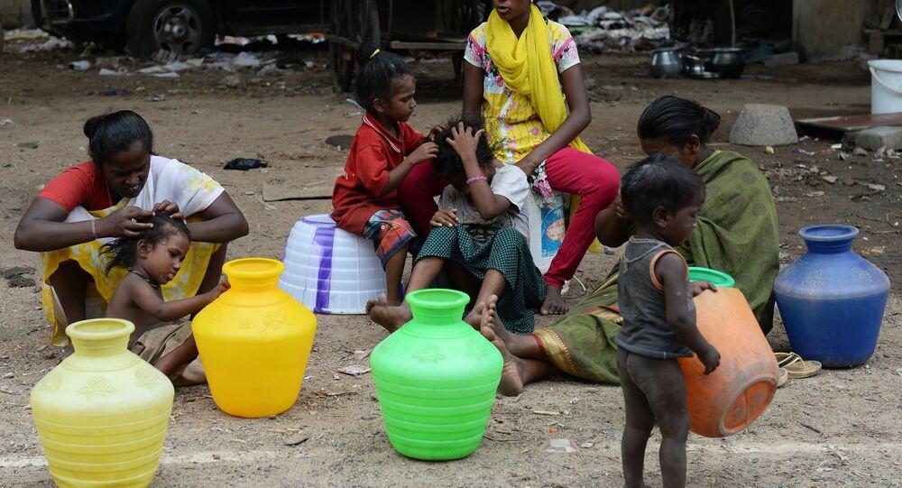 Mulheres sem-teto na Índia sob um ponte com suas crianças aguardam para coletar água em um caminhão de distribuição em Chennai, em 8 de junho de 2017.