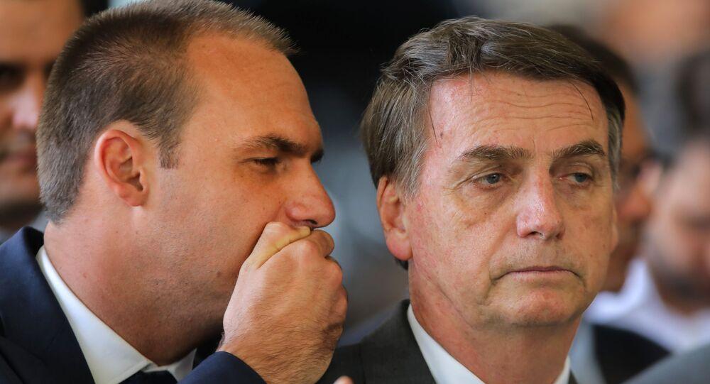 Eduardo Bolsonaro cochicha no ouvido do pai Jair Bolsonaro no comitê de transição de governo em Brasília, 14 de novembro de 2018