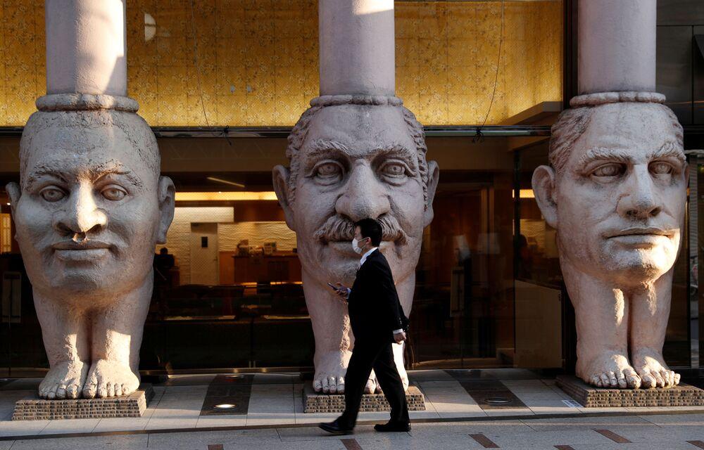 Homem caminha ao lado de colunas gigantescas feitas em forma de rostos humanos instaladas cerca do hotel Dotonbori em Osaka, Japão
