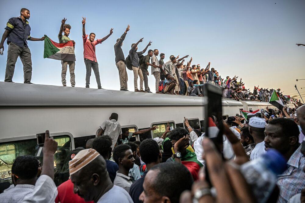 Manifestantes sudaneses no teto de um trem no decurso dos confrontos entre a oposição e o Conselho Nacional de Transição