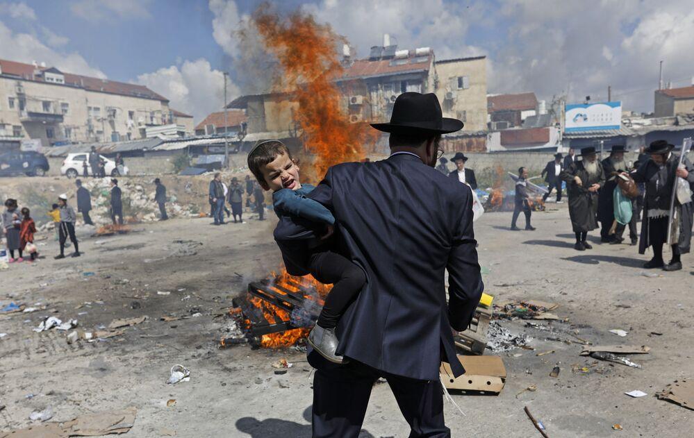Judeu ultraortodoxo levando criança durante o ritual na véspera do Pessach (Páscoa judaica), em Jerusalém