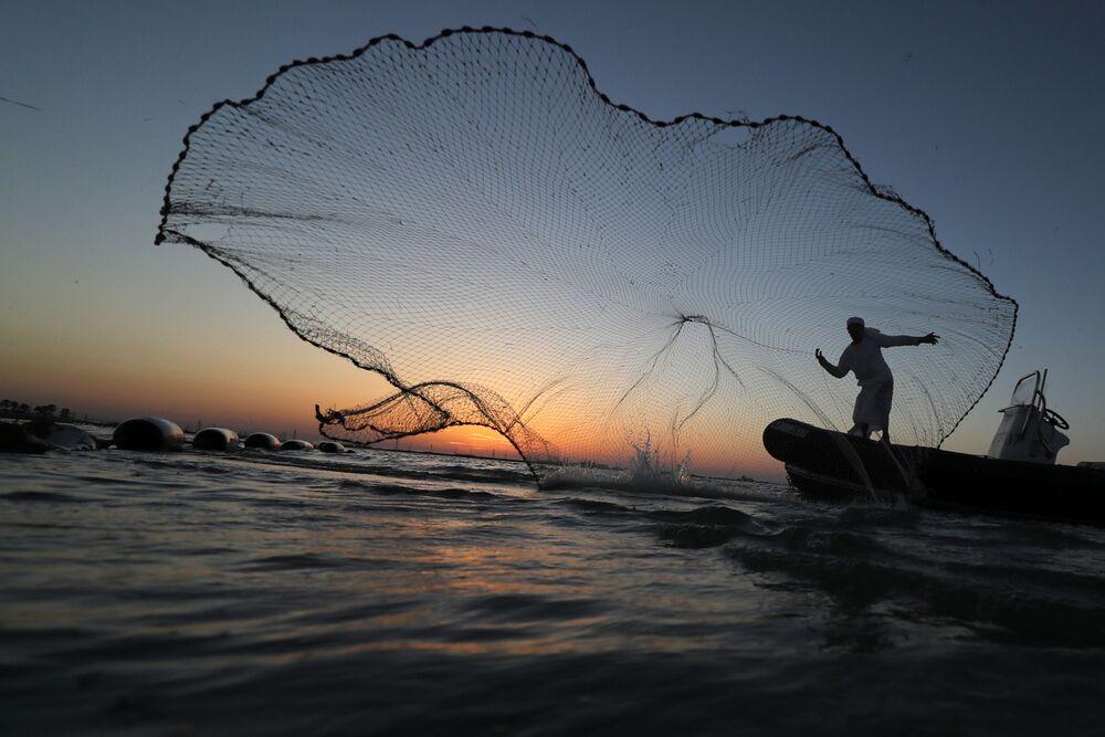 Pescador lança rede a partir de seu barco perto da costa de Abu Dhabi, Emirados Árabes Unidos