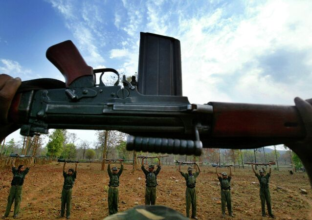 Naxalistas, oficialmente o Partido Comunista da Índia (Maoísta) levantam suas armas durante um exercício em uma base temporária nas florestas de Abujh Marh, no estado de Chhattisgarh, na Índia.