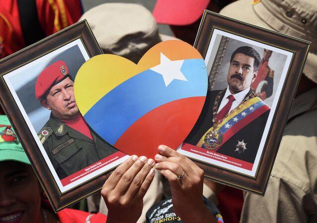 Apoiador(a) do presidente venezuelano, Nicolás Maduro, exibe imagens do atual chefe de Estado e de seu antecessor, Hugo Chávez, durante manifestação em Caracas no Dia do Trabalhador