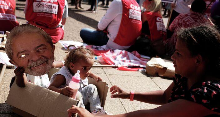 Filha de um sindicalista segura uma máscara representando o ex-presidente Luiz Inácio Lula da Silva durante uma manifestação do Dia do Trabalho em São Paulo, Brasil, em 1º de maio de 2019.