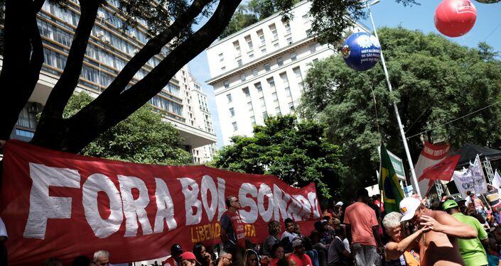 Sindicalistas seguram uma faixa com Fora Bolsonaro durante um comício em São Paulo.