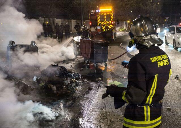 Bombeiros extinguem lixeiras incendiadas após um protesto contra a brutalidade policial no subúrbio parisiense de Bobigny.
