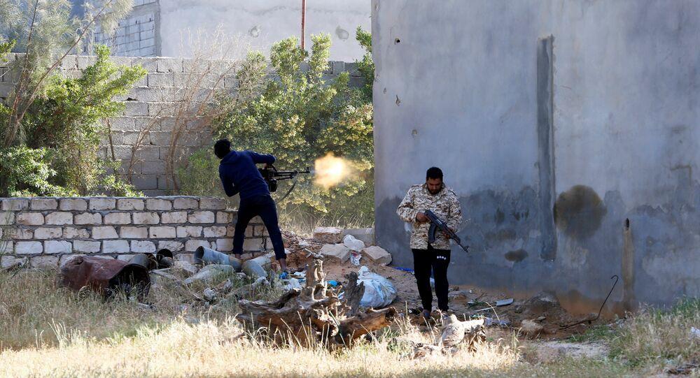 Um membro das forças governamentais reconhecidas internacionalmente na Líbia dispara durante uma luta contra forças orientais em Ain Zara, Trípoli.