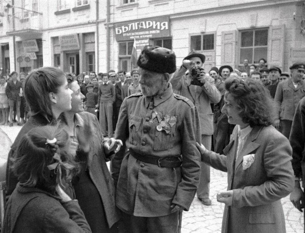 Veterano da Guerra da Turquia fala com meninas em uma cidade búlgara, libertada dos nazistas