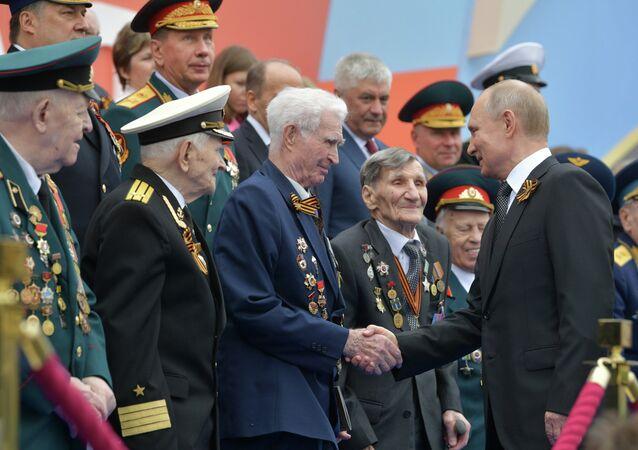 Presidente da Rússia, Vladimir Putin, saúda os veteranos antes do início da parada militar que se realiza anualmente na Praça Vermelha em comemoração da vitória na Grande Guerra pela Pátria (parte da Segunda Guerra Mundial, compreendida entre 22 de junho de 1941 e 9 de maio de 1945, e limitada às hostilidades entre a União Soviética e a Alemanha nazista e seus aliados)