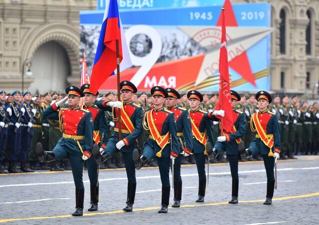 Soldados carregando a Bandeira da Vitória e da bandeira nacional russa