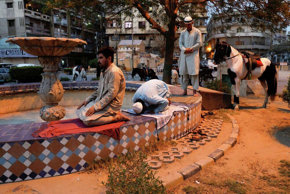 Homens fazem as orações da noite ao lado de uma fonte depois de quebrar o jejum (iftar) no Ramadã, em Karachi, Paquistão, 8 de maio de 2019.