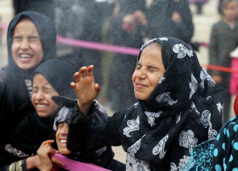 Meninas iemenitas reagem ao serem borrifadas com água por voluntárias no mês sagrado do Ramadã em Sanaa, Iêmen 8 de maio de 2019.