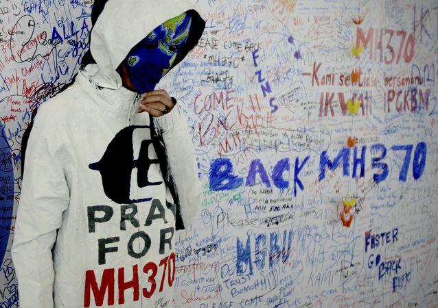 Pessoa não identificada usa máscara representando o voo MH370 desaparecido da Malaysia Airlines
