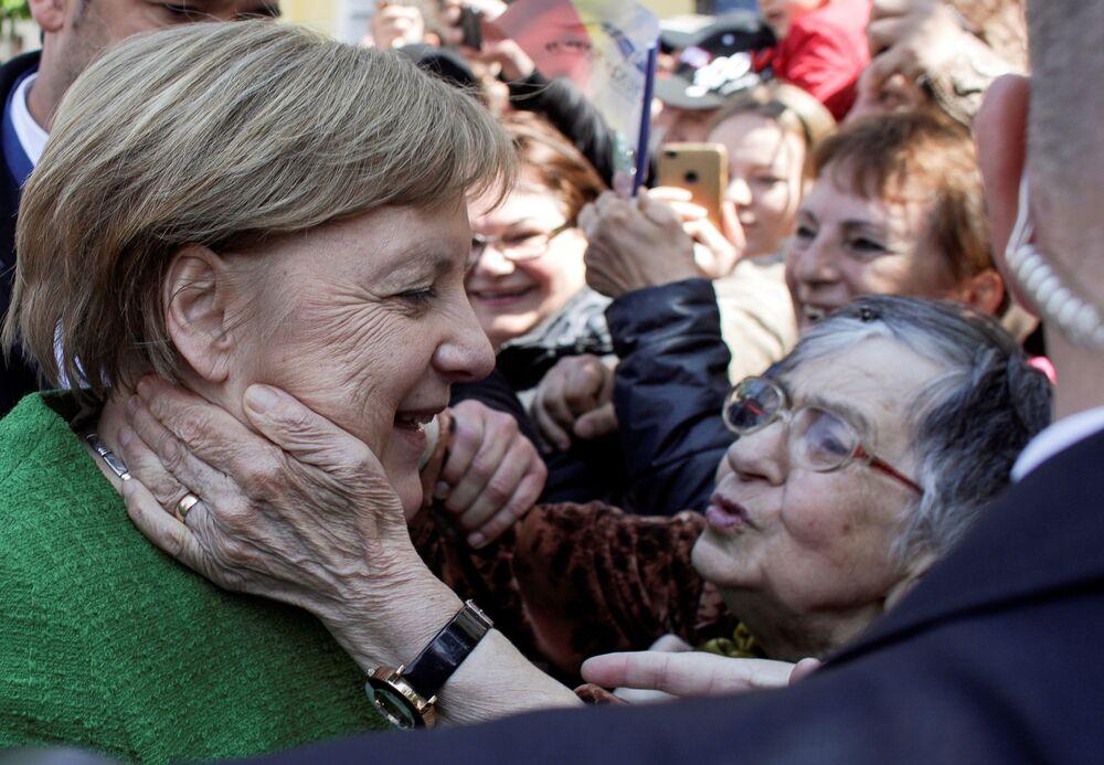 """Chanceler alemã, Angela Merkel, cumprimenta as pessoas depois de posar para uma """"foto de família"""" durante a reunião informal dos líderes da União Europeia em Sibiu, Romênia"""