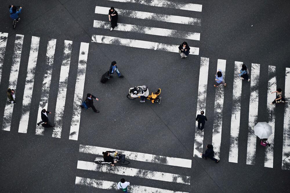Pedestres atravessam uma rua do bairro Ginza, Japão