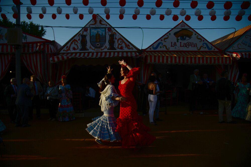 Mulheres dançam durante festival o Feira de Abril em Sevilha