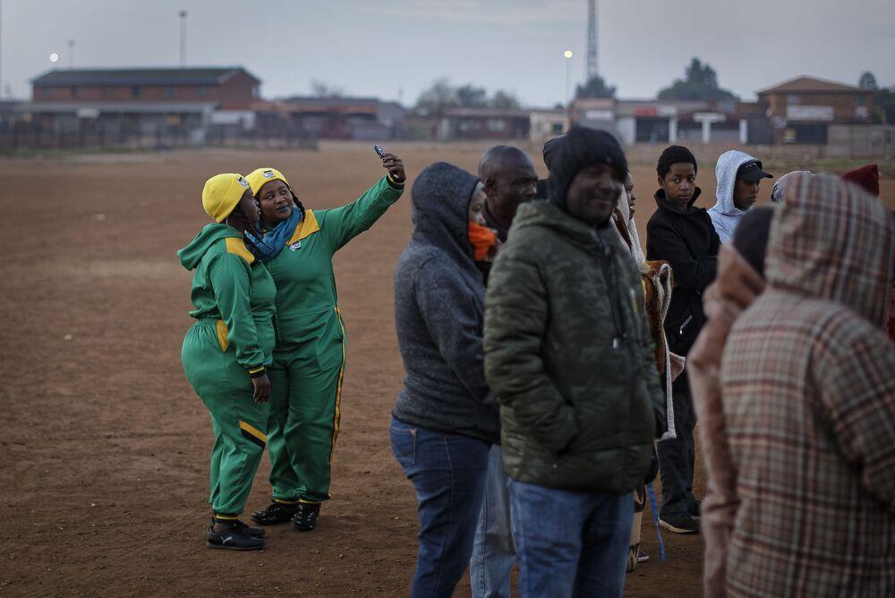 Dois apoiadores do Congresso Nacional Africano tiram selfies enquanto fazem fila para votar no povoado de Bekkersdal a oeste de Johanesburgo, na África do Sul