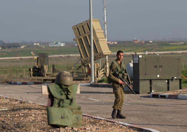 Um soldado israelense guarda o sistema de defesa aérea Iron Dome (Cúpula de Ferro), implantado nas colinas de Golã, perto da fronteira com a Síria.