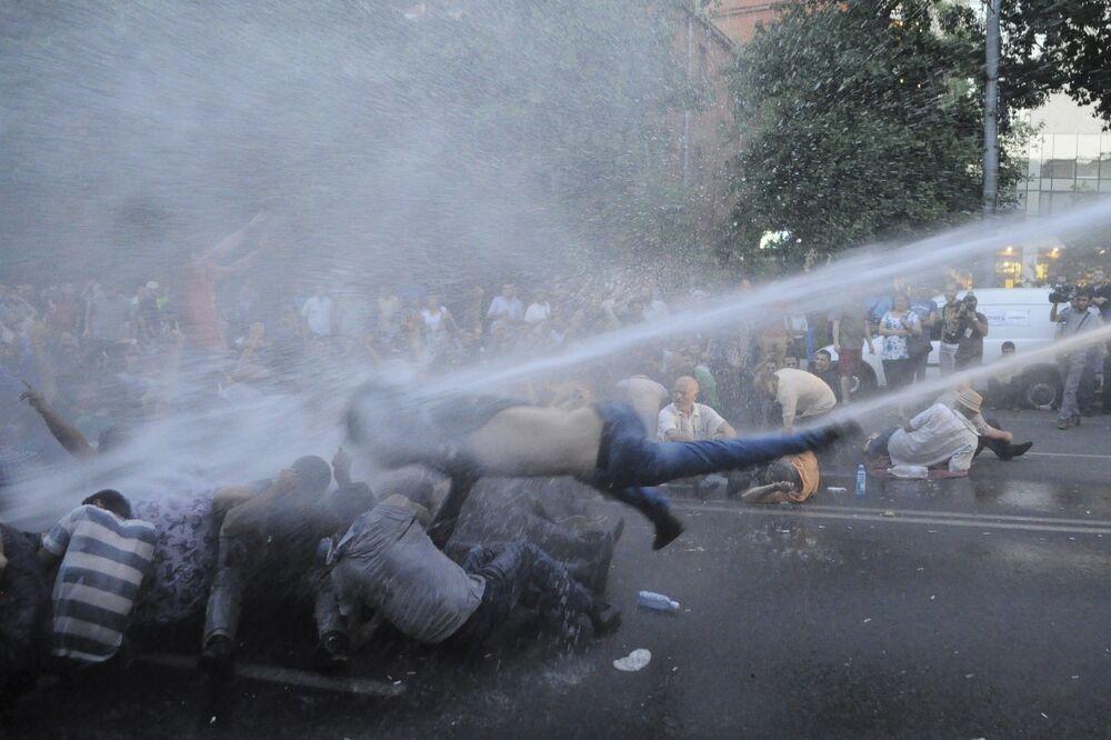 Manifestantes atingidos por um jato de água lançado de um veículo de polícia durante o protesto contra o aumento das tarifas de energia em Erevan, capital da Armênia, em 22 de junho de 2015.