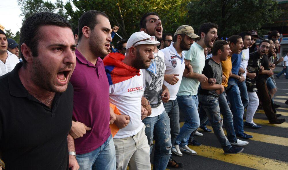 Manifestantes gritam andando pelas ruas durante o protesto contra o aumento das tarifas de energia em Erevan, capital da Armênia, em 22 de junho de 2015.