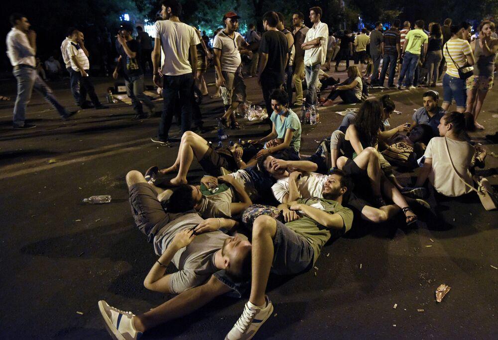 Manifestantes deitaram-se no chão durante o protesto contra o aumento das tarifas de energia em Erevan, capital da Armênia, em 22 de junho de 2015.