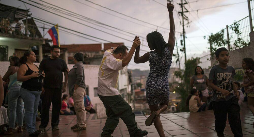 Pessoas dançando em uma praça em Caracas, Venezuela