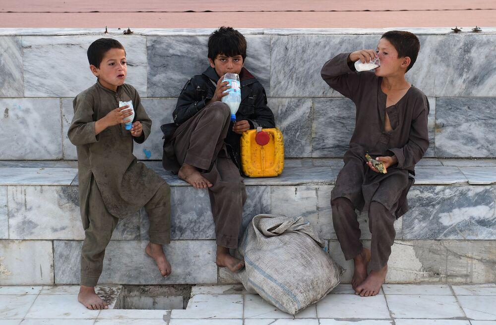 Meninos afegãos tomam bebidas de iogurte no pátio da Mesquita Azul em Mazar-e-Sharif durante o Ramadão