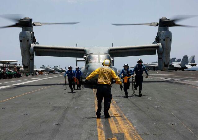 Militares retiram calços e cabos da aeronave multifunção MV-22 Osprey do Esquadrão Marine Medium Tiltrotor 264, no convés do porta-aviões USS Abraham Lincoln de classe Nimitz, durante as manobras em 17 de maio de 2019