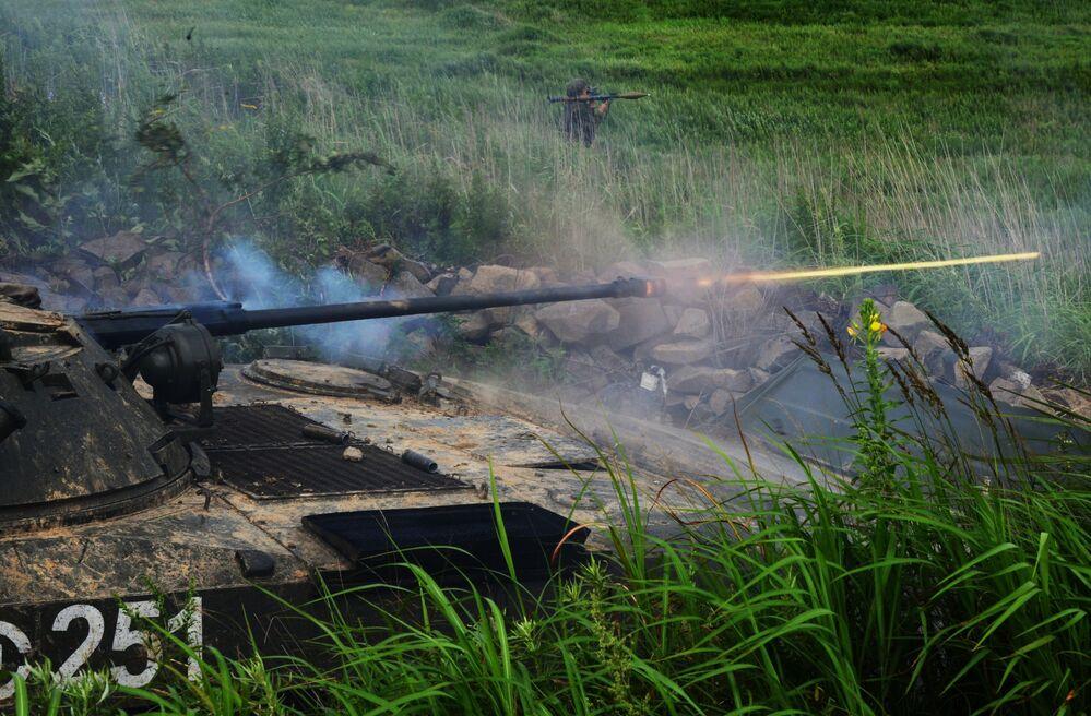 Veículo de combate de infantaria BMP-2 e um soldado com lança-granadas nas manobras tácticas dos fuzileiros navais no polígono de Klerk na região de Primorie, 2018