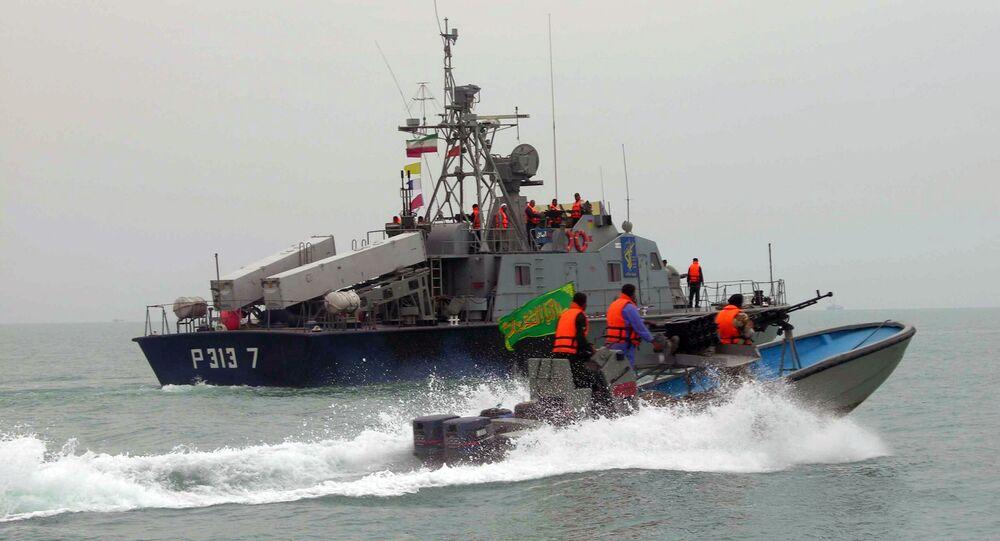 Membros da Guarda Revolucionária Irã navegam junto a uma embarcação iraniana durante manobras ao longo do mar do Golfo e do mar de Omã.