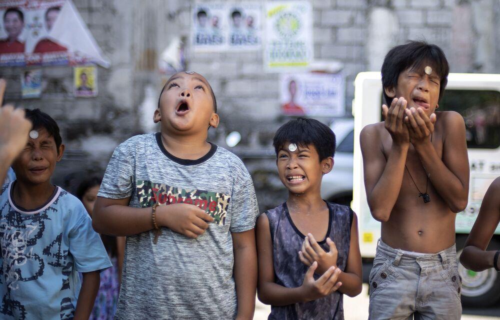 Meninos contorcem rosto enquanto participam de jogo em que precisam deslizar uma moeda da testa para a boca para vencer, durante a Festa de Santa Rita de Cássia, em Manila, 19 de maio de 2019